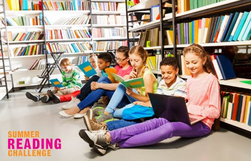 Showing group of children sitting reading books in library